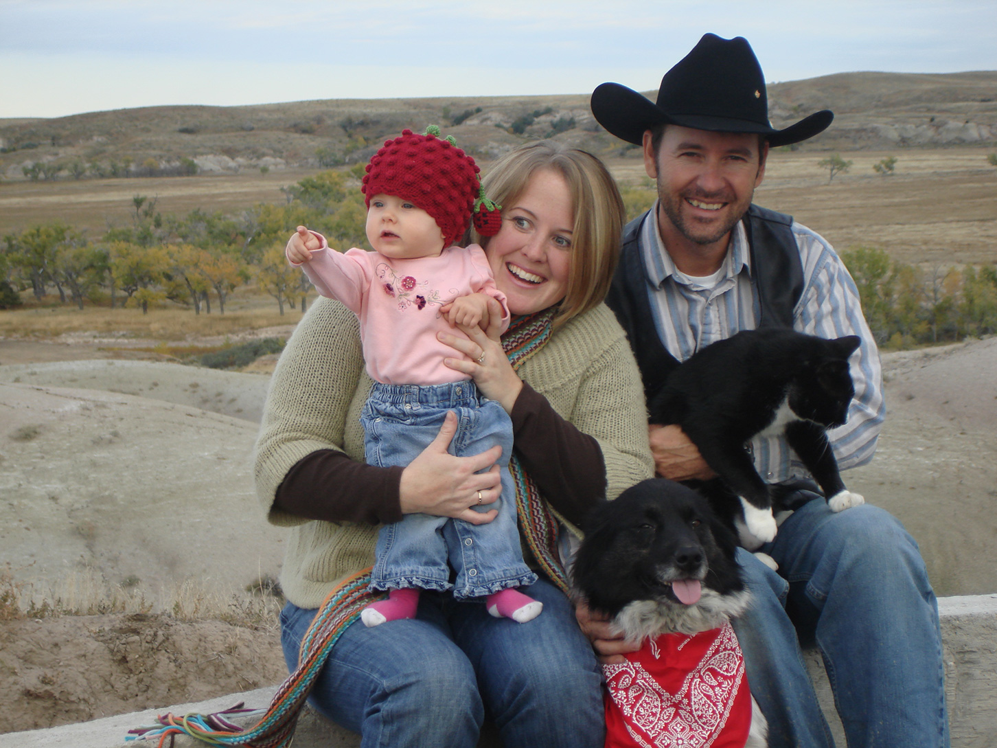 Man in a cowboy had sitting on a wall with wman holding a baby, with a black dog and cat in front