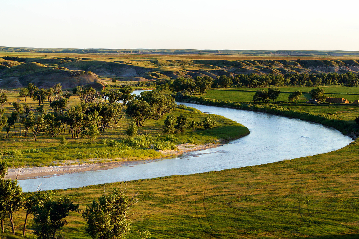Badlands with a river flowing between grassy plains