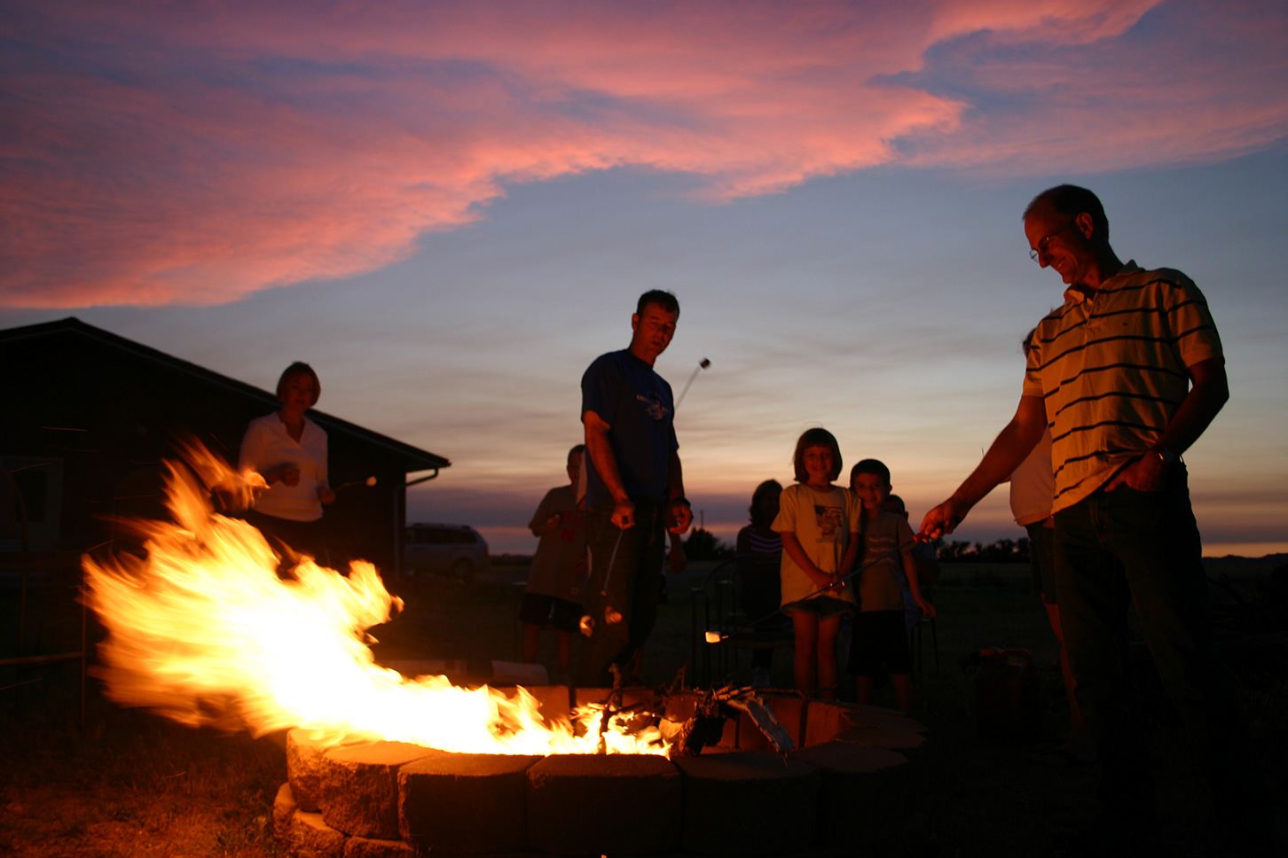 Family around an open fire at dusk cooking mashmellows